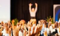 an assembly of students raising hands at school